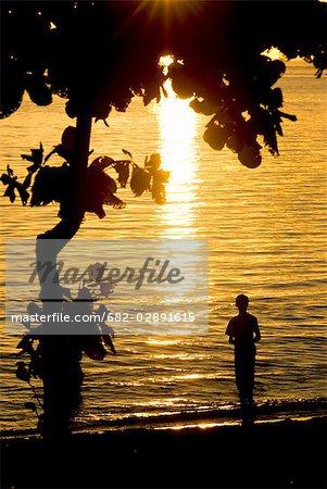 Une silhouette d'un garçon solitaire, debout au bord de l'eau au coucher du soleil, île Maurice