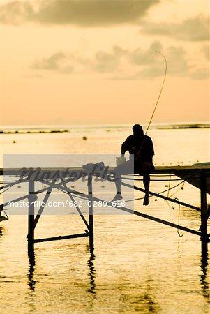 Une silhouette d'un pêcheur assis sur un ponton au coucher du soleil, île Maurice