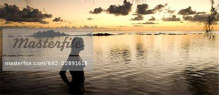 Un touriste observe le coucher de soleil sur les affleurements rocheux à l'île Maurice
