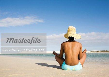 Vue arrière du topless femme assise sur la plage de méditation, des aiguilles, Province occidentale du Cap, en Afrique du Sud
