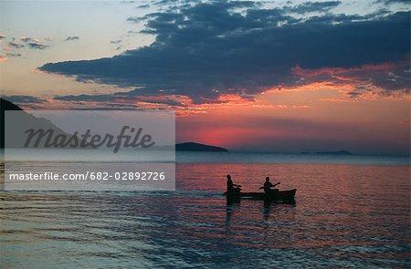 Deux personnes dans un canot de Dug-out au coucher du soleil