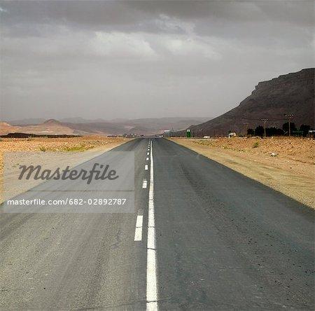 Double route asphaltée traversant la zone aride sur une journée nuageuse