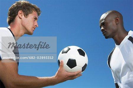 Deux hommes Face à Face et ballon de football Holding
