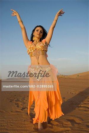 Jeune danseuse du ventre dansant dans le désert