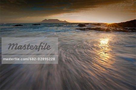 Coucher du soleil de montagne de la table avec les configurations de vagues, Bloubergstrand, Cape Town, Western Cape Province, Afrique du Sud