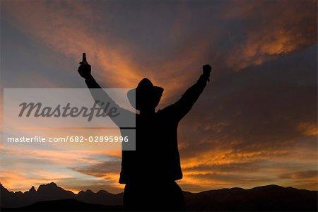 Un jeune homme coiffé d'un chapeau lève ses bras au coucher du soleil, du Drakensberg, Kwazulu Natal, Afrique du Sud
