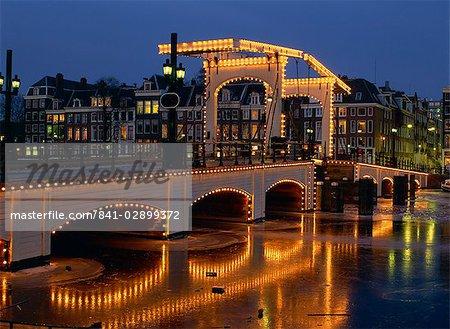 Lumières sur le Magere Brug (pont maigre) qui se reflètent dans le canal, en hiver à Amsterdam, Hollande, Europe