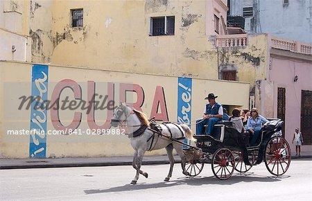 Touristes dans une calèche en passant un mur signent disant « Live Cuba libre », la Havane, Cuba, Antilles, Amérique centrale