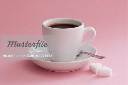 Tasse de café avec des morceaux de sucre en forme de coeur