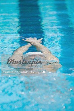 Jeune nageur faisant dos crawlé sous l'eau