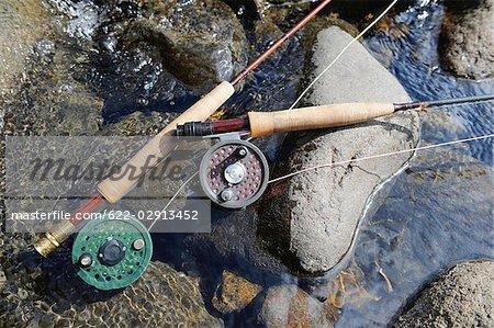 Poignée de la canne à pêche et un moulinet sur l'eau