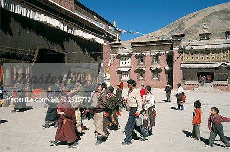 Pilgrims in monastery courtyard,. Sakya, Tibet, China, Asia