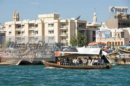 Abra (cross creek ferry) chugs passé dhow quais et des bâtiments modernes de Deira, Dubai Creek, Dubaï, Émirats Arabes Unis, Moyen-Orient