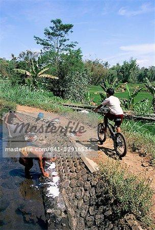 Ladies washing in canal near Candi Suimberawan, island of Java, Indonesia, Southeast Asia, Asia
