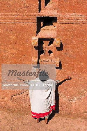 Pèlerin avec bras tendus prier sous windows sur église monolithique de pari Maryam (Sainte-Marie) de l'église, considéré comme la plus ancienne église de rupestres de Lalibela, Ethiopie, Afrique