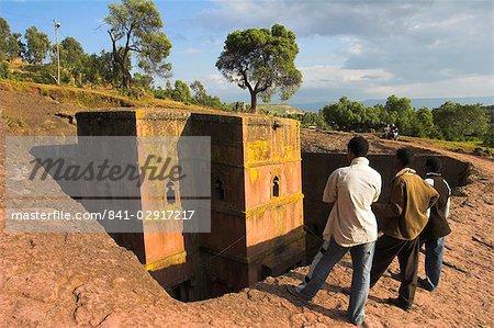 Hommes qui cherchaient à rupestres monolithique église de Ghiorghis (St. George) de, 40 pieds de hauteur avec toit en forme de croix grecque, le plus célèbre de l'Afrique de Lalibela (Éthiopie), églises, patrimoine mondial UNESCO de Lalibela