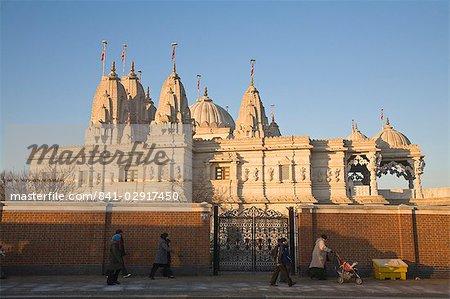 People walking past Shri Swaminarayan Mandir Temple, the largest Hindu temple outside India, winner of UK Pride of Place award 2007, Neasden, London, England, United Kingdom, Europe