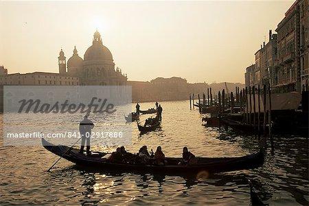 Coucher de soleil vue sur le Grand Canal, à l'église de Santa Maria Della Salute avec gondoliers en silhouette, Venise, Vénétie, Italie, Europe