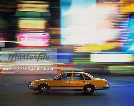 Passé au volant de Yellow cab floue néons nuit à Times Square à New York, États-Unis d'Amérique, l'Amérique du Nord