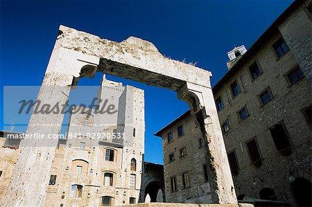 Towers lining the Piazza della Cisterna, framed by stone well, San Gimignano, Tuscany, Italy, Europe