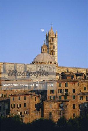 Mond am Himmel über Kathedrale und Häuser gruppierten unten bei Sonnenuntergang, Siena, Toskana, Italien, Europa
