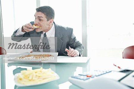 Kaufmann Essen Pizza mit Pommes frites am Schreibtisch