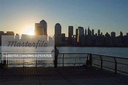 Pêcheur pêche à partir d'un quai de la ville de Jersey à l'aube, face à la Manhattan skyline, Jersey City, New Jersey, États-Unis d'Amérique, l'Amérique du Nord