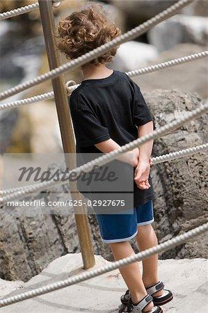 Vue arrière d'un garçon debout sur les marches, les mains derrière le dos, Riviera italienne, Parc National des Cinque Terre, Vernazza, La Spezia, Ligurie, Italie