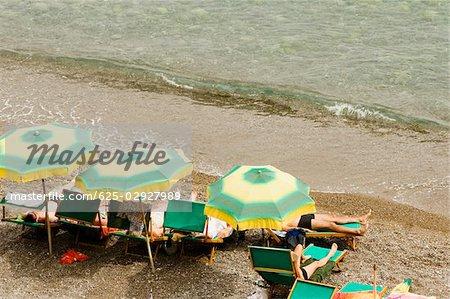 High angle view of tourists relaxing on lounge chairs, Spiaggia Grande, Positano, Amalfi Coast, Salerno, Campania, Italy