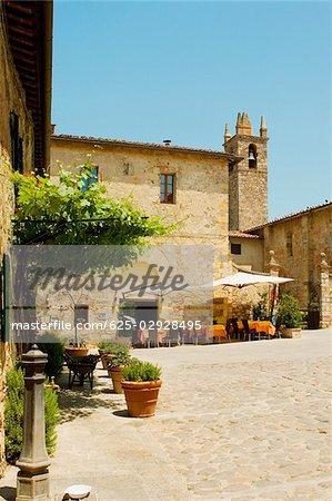 Sidewalk cafe beside a church, Romanesque Church, Piazza Roma, Monteriggioni, Siena Province, Tuscany, Italy