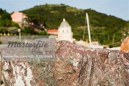 Gros plan d'une roche avec une église dans le fond, l'église de Santa Margherita Antioche, Riviera italienne, Cinque Terre Parc National, Vernazza, La Spezia, Ligurie, Italie