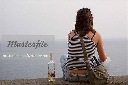 Rear view of a woman sitting at seaside with a wine bottle, Corniglia, Cinque Terre, La Spezia, Liguria, Italy