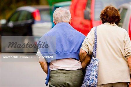 Rear view of a senior couple walking with arm in arm, Corniglia, Italian Riviera, Cinque Terre National Park, Vernazza, La Spezia, Liguria, Italy