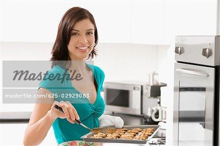 Portrait d'une jeune femme tenant un plateau de biscuits et souriant