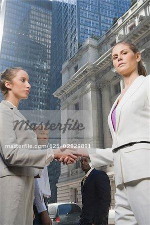 Zwei Geschäftsfrauen Händeschütteln mit zwei Geschäftsleute stehen im Hintergrund