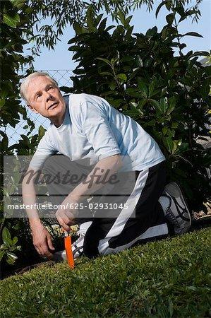 Senior homme à genoux dans un jardin et tenant une fourche de jardinage