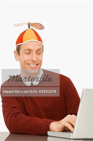 Homme d'affaires portant un bonnet d'hélice et travaillant sur un ordinateur portable
