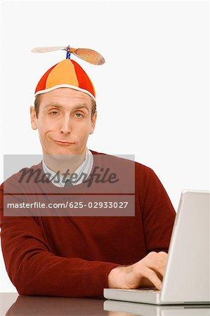 Portrait d'un homme d'affaires portant un bonnet d'hélice et travaillant sur un ordinateur portable