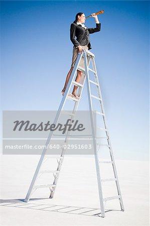 femme d'affaires sur une échelle avec une longue-vue