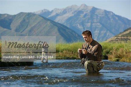 fly fisherman fishing in a mountain river