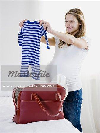 femme enceinte brandissant des vêtements pour bébé