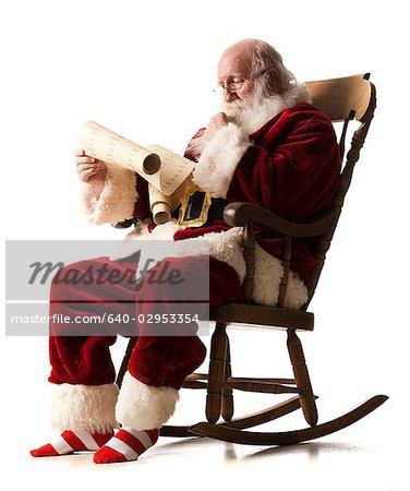 assis dans un fauteuil à bascule passe sur sa liste du père Noël
