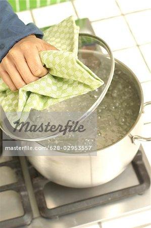 Femme de cuisson sur la cuisinière à gaz