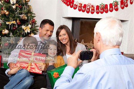 Grand-père prise de photo de famille à l'arbre de Noël