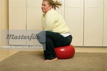 Surpoids jeune femme aux cheveux blonds est assis sur un ballon de fitness