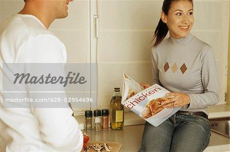 Brownhaired Frau in einem Kochbuch zu lesen, während ihr Freund ist die Zutaten - Küche kochen - Common Ground - schneiden