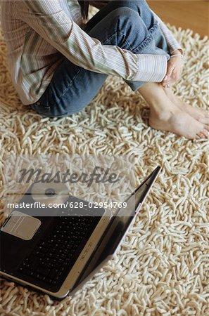 Frau sitzt neben einem Laptop mit ihren Beinen Barfooted festgezogen zu ihrem Körper - Wohnzimmer - Startseite
