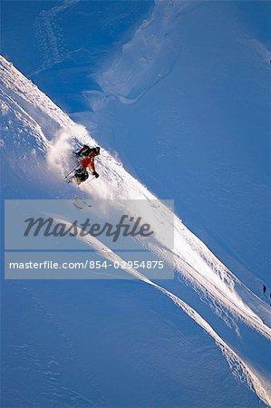 Extreme skier skis down steep snow covered mountain Chugach Mountains Southcentral Alaska Winter