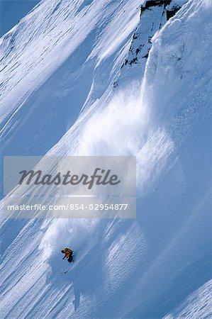 Extreme skier skis down steep snow covered mountain Chugach Mountains Valdez Southcentral Alaska Winter