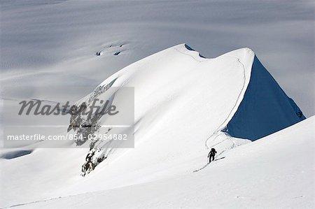 Skieur grimper sur une crête surplombant le printemps Sargent Icefield centre-sud de l'Alaska